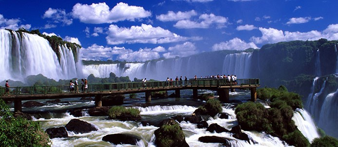 O conjunto de quedas das Cataratas do Iguaçu é uma das maravilhas naturais do planeta. É um símbolo da natureza exuberante do Brasil – uma enorme quantidade de água cercada de mata tropical nativa - que atrai milhares de turistas de todo o mundo para Foz do Iguaçu. No entanto, há muito mais para se ver e fazer na cidade. No Parque Nacional do Iguaçu, onde ficam as cataratas, há emocionantes passeios de barco e trilhas que percorrem a exuberante mata nativa. Existe também a opção de se conhecer tudo isso do alto, por meio de um vôo de helicóptero. Foz do Iguaçu (PR). 1999. Christian Knepper / Embratur *** Local Caption *** PT: Autorizado o uso exclusivo para divulgação do produto turístico  brasileiro